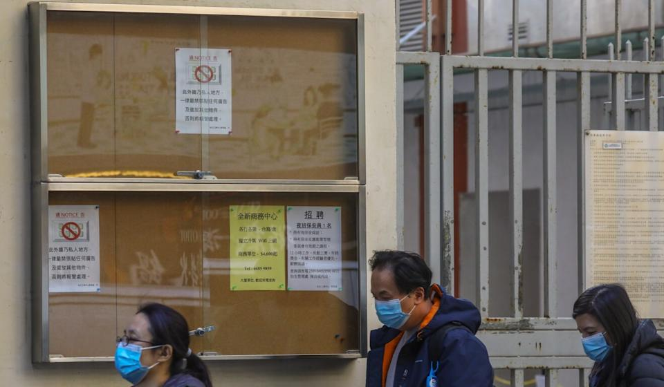 People file pass a job notice board in Kwun Tong on Monday. Photo: Dickson Lee