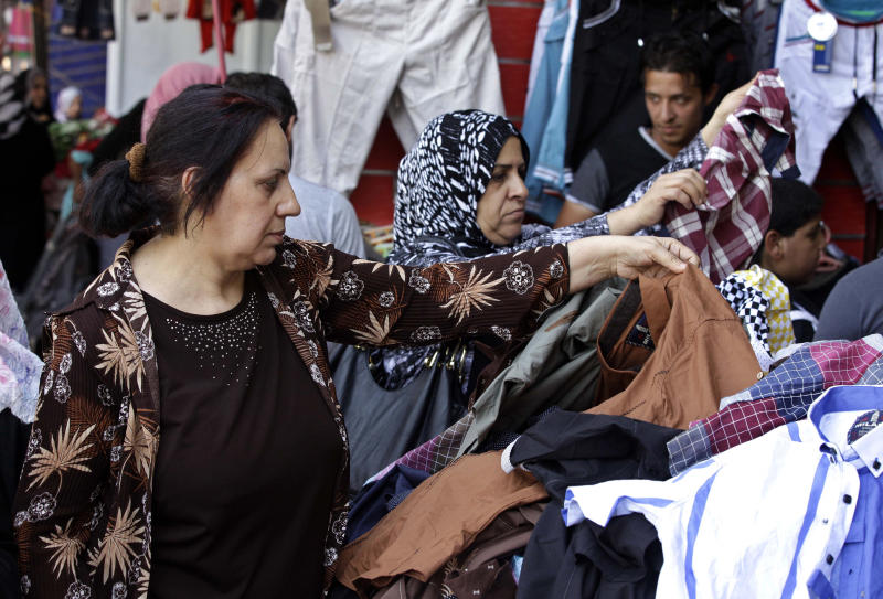Iraqis buy clothes for Eid al-Fitr at the Shorjah market in central Baghdad, Iraq, Tuesday, Aug. 6, 2013. Eid al-Fitr marks the end of the holy fasting month of Ramadan. (AP Photo/Karim Kadim)