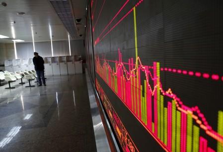 An investor looks at an electronic screen showing stock information at a brokerage house in  Beijing