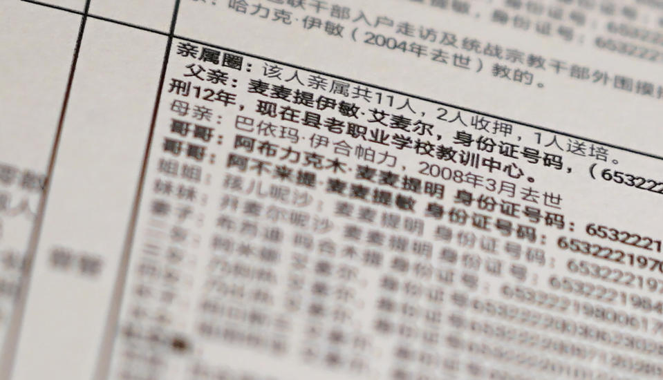 """This Sunday, Feb. 16, 2020 photo shows details from a print of a leaked database obtained by The Associated Press. Text reads, """"Family circle: Total relatives 11, 2 imprisoned, 1 sent to training, Father: Memtimin Emer... sentenced to 12 years, is now in the training center at the old vocational school."""" The database offers the fullest and most personal view yet into how Chinese officials decided who to put into and let out of detention camps, as part of a massive crackdown that has locked away more than a million ethnic minorities, most of them Muslim. (AP Photo)"""