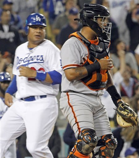 The Los Angeles Dodgers' Bobby Abreu crosses the plate to tie the score, followed shortly by Juan Uribe for the go-ahead run as San Francisco Giants catcher Hector sanchez watches the infield in the sixth inning of a National League baseball game in Los Angeles Monday, May 7, 2012. The Dodgers won, 9-1 (AP Photo/Reed Saxon)