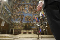 "Gianni Crea, the Vatican Museums chief ""Clavigero"" key-keeper, walks through the Sixtine Chapel as he opens the museum, at the Vatican, Monday, Feb. 1, 2021. Crea is the ""clavigero"" of the Vatican Museums, the chief key-keeper whose job begins each morning at 5 a.m., opening the doors and turning on the lights through 7 kilometers of one of the world's greatest collections of art and antiquities. The Associated Press followed Crea on his rounds the first day the museum reopened to the public, joining him in the underground ""bunker"" where the 2,797 keys to the Vatican treasures are kept in wall safes overnight. (AP Photo/Andrew Medichini)"