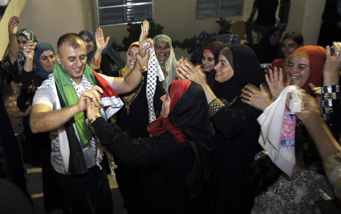 Palestinian released prisoner Burhan Sbeih, left, dances with relatives at his home in the West Bank village of Kofr Raei near Jenin city after his release, Wednesday, Aug. 14, 2013. Israel released 26 Palestinian inmates, including many convicted in grisly killings, on the eve of long-stalled Mideast peace talks, angering families of those slain by the prisoners, who were welcomed as heroes in the West Bank and Gaza. (AP Photo/Mohammed Ballas)