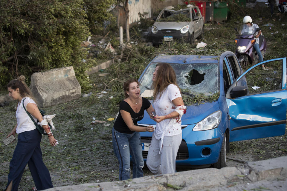 Injured stand after of a massive explosion in Beirut, Lebanon, Tuesday, Aug. 4, 2020. Massive explosions rocked downtown Beirut on Tuesday, flattening much of the port, damaging buildings and blowing out windows and doors as a giant mushroom cloud rose above the capital. Witnesses saw many people injured by flying glass and debris. (AP Photo/Hassan Ammar)