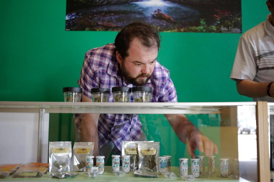 """Bud tender"" Ryan Huntington stocks up a display case with products as The Cannabis Corner, the first city-owned recreational marijuana store in the country, makes preparations for their grand opening in North Bonneville, Washington March 6, 2015. REUTERS/Jason Redmond  (UNITED STATES - Tags: BUSINESS POLITICS DRUGS SOCIETY)"