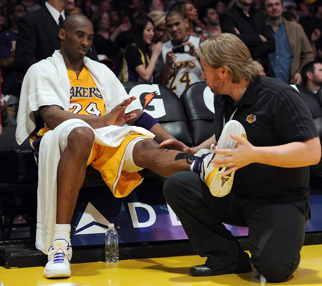 LOS ANGELES, CA - APRIL 06:  Kobe Bryant #24 of the Los Angeles Lakers receives help from a trainer during a timeout in the game against the Houston Rockets at Staples Center on April 6, 2012 in Los Angeles, California.  The Rockets won 112-107.  NOTE TO USER: User expressly acknowledges and agrees that, by downloading and or using this photograph, User is consenting to the terms and conditions of the Getty Images License Agreement.  (Photo by Harry How/Getty Images)