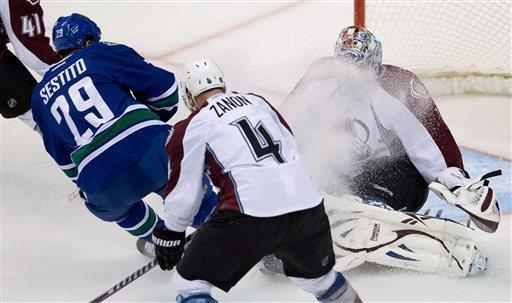 Vancouver Canucks' Tom Sestito, left, showers Colorado Avalanche goalie Semyon Varlamov, of Russia, with ice as he comes to a stop to avoid a collision while Colorado's Greg Zanon (4) defends during the second period of an NHL hockey game in Vancouver, British Columbia, on Thursday, March 28, 2013. (AP Photo/The Canadian Press, Darryl Dyck)