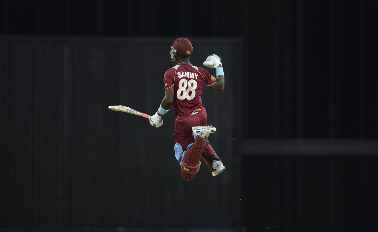 West Indies' Darren Sammy leaps to celebrate after the West Indies won their second T20 international cricket match against England at Kensington Oval in Bridgetown, Barbados March 11, 2014. REUTERS/Philip Brown (BARBADOS - Tags: SPORT CRICKET)