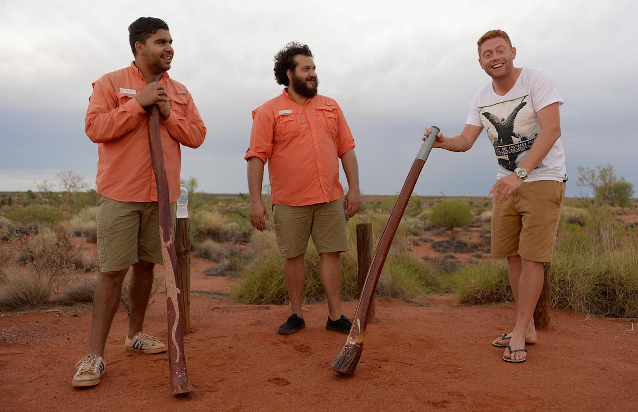 AYERS ROCK, AUSTRALIA - NOVEMBER 26:  Jonathan Bairstow of England tries his hand at playing a didgeridoo during a team visit to Uluru, which is also known as Ayers Rock, on November 26, 2013 in Ayers Rock, Australia.  (Photo by Gareth Copley/Getty Images)