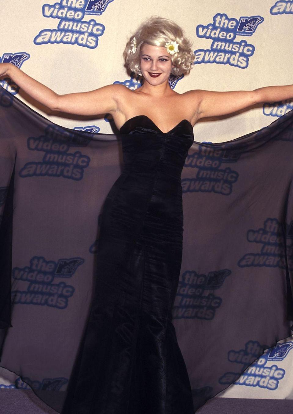 <p>With a dark lip and bright flowers in her hair, Drew Barrymore is bringing loads of contrast and fashun to the 1995 awards show. </p>
