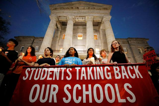 <p>High school students hold candles in memory of the victims of the shooting at Marjory Stoneman Douglas High School as they stand in front of the North Carolina State Capitol building during a march for safer gun laws at dusk in Raleigh, N.C., Feb. 20, 2018. (Photo: Jonathan Drake/Reuters) </p>
