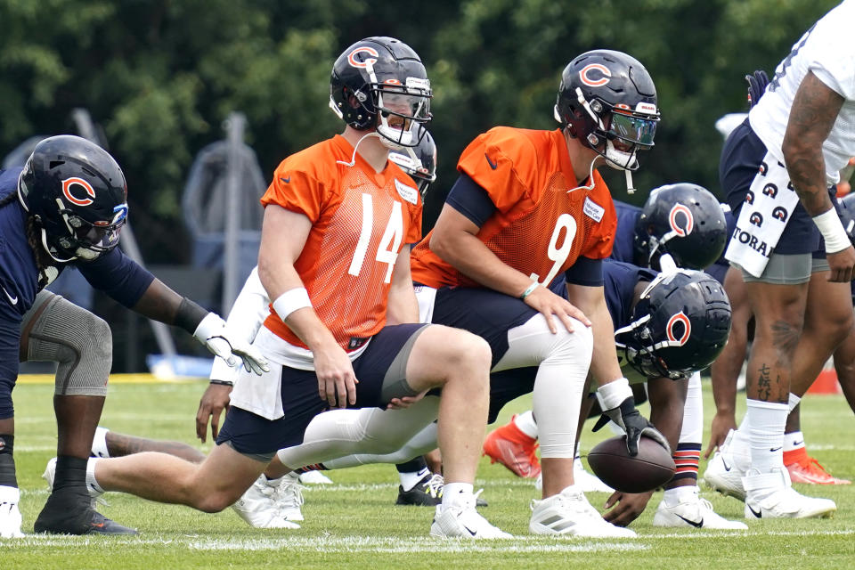 Chicago Bears quarterbacks Andy Dalton (14) and Nick Foles (9) stretch with teammates during NFL football practice in Lake Forest, Ill., Wednesday, July 28, 2021. (AP Photo/Nam Y. Huh)