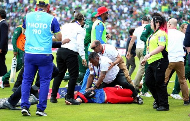 A pitch invader is tackled by security at Headingley