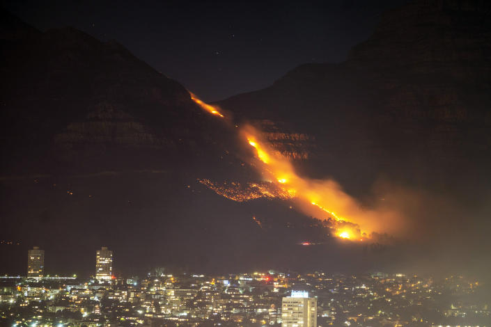 Residential neighborhoods are lit by raging fires in Cape Town, South Africa, Monday, April 19, 2021. Residents are being evacuated from Cape Town neighborhoods after a huge fire spreading on the slopes of the city's famed Table Mountain was fanned by strong winds overnight and threatened houses.(AP Photo/Jerome Delay)
