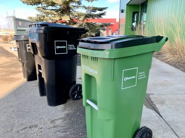 Carts like these — black for garbage and green for food scraps — are being distributed to Edmonton homes as part of a new waste collection system.  (Adrienne Lamb/CBC - image credit)