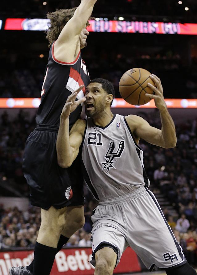 San Antonio Spurs' Tim Duncan (21) is defended by Portland Trail Blazers' Robin Lopez, left, as he tries to shoot during the first half on an NBA basketball game, Friday, Jan. 17, 2014, in San Antonio. (AP Photo/Eric Gay)