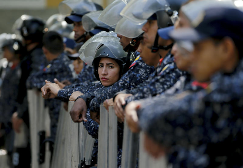 Police stand guard in anticipation of a march called by a coalition of opposition parties and civic groups who are petitioning lawmakers for a law of guarantees that will protect workers who have been victims of political retaliation and unjustified dismissals, in Caracas, Venezuela, Tuesday, March 19, 2019. (AP Photo/Fernando Llano)