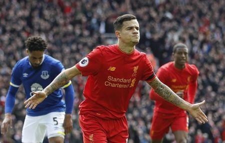Liverpool's Philippe Coutinho celebrates scoring their second goal as Everton's Ashley Williams (L) looks dejected