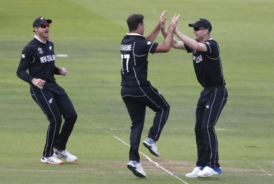 New Zealand's Colin de Grandhomme, centre, celebrates after taking the wicket of England's Joe Root during the Cricket World Cup final match between England and New Zealand at Lord's cricket ground in London, Sunday, July 14, 2019. (AP Photo/Alastair Grant)
