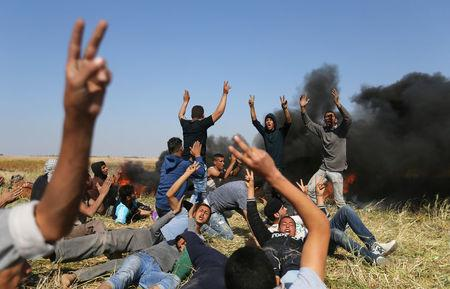 Palestinians shout during clashes with Israeli troops at the Gaza-Israel border at a protest demanding the right to return to their homeland, in the southern Gaza Strip March 31, 2018. REUTERS/Ibraheem Abu Mustafa