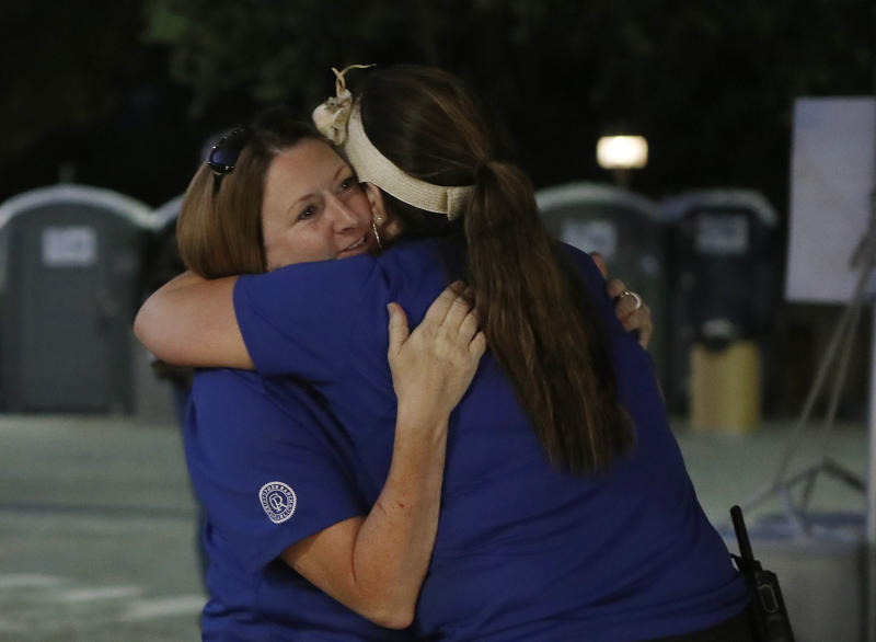 Gilroy Garlic festival volunteer Denise Buessing, left, embraces fellow volunteer Marsha Struzik at a reunification center in a parking lot at Gavilan College following a deadly shooting at the annual food festival (Picture: AP)