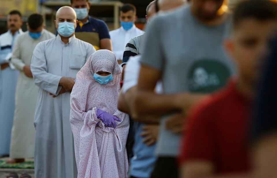 A girl attends Eid al-Adha prayers with other worshipers on the street outside Abu Hanifa mosque in Baghdad Adhamiya district, during the outbreak of the coronavirus disease (COVID-19), in Iraq, July 31, 2020. REUTERS/Thaier Al-Sudani