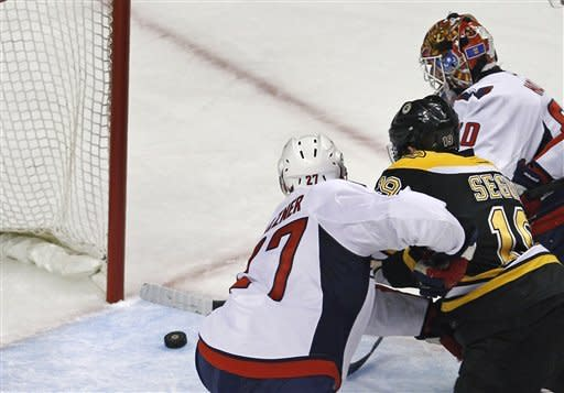Boston Bruins center Tyler Seguin (19) threads between Washington Capitals goalie Braden Holtby, top, and defenseman Karl Alzner for a goal during the second period of Game 7 of an NHL hockey Stanley Cup first-round playoff series, in Boston on Wednesday, April 25, 2012. (AP Photo/Charles Krupa)