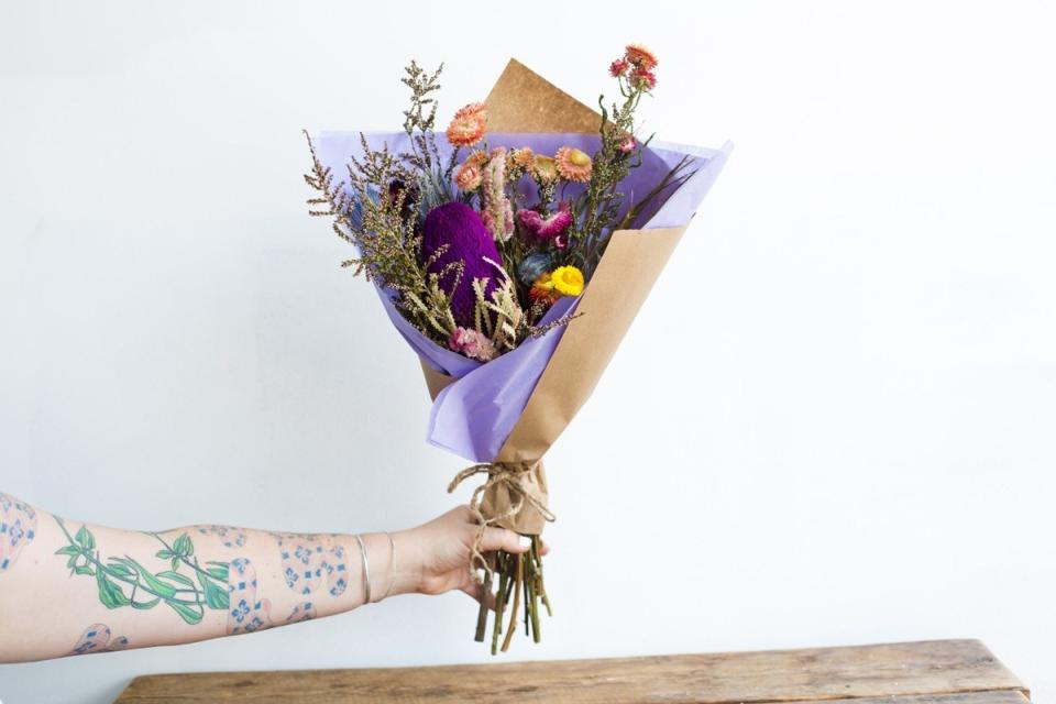 white tattooed arm holding dried bouquet