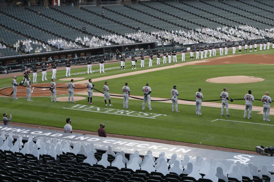 The Chicago White Sox, top, and Minnesota Twins hold a black ribbon for social justice before the White Sox's home opener baseball game Friday, July 24, 2020, in Chicago. (AP Photo/Charles Rex Arbogast)