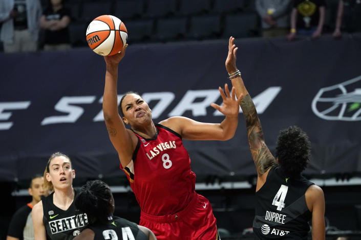 Las Vegas Aces' Liz Cambage (8) tries to get a shot off as Seattle Storm's Candice Dupree (4) defends in the first half of a WNBA basketball game Saturday, May 15, 2021, in Everett, Wash. (AP Photo/Elaine Thompson)