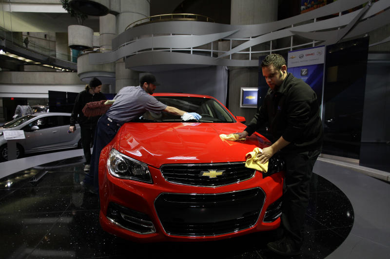 Workers polish a Chevrolet SS Sedan displayed at the General Motors headquarters in Detroit, on April 1, 2014