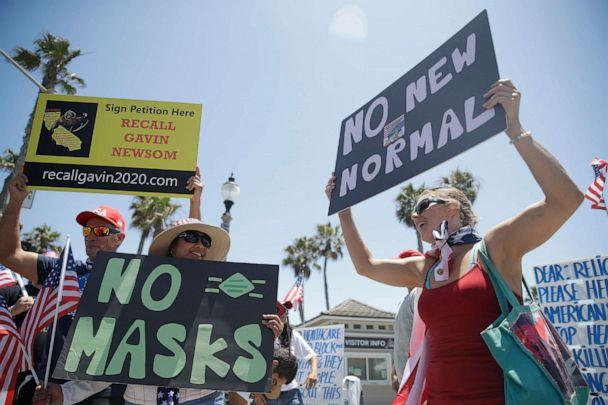 PHOTO: Demonstrators hold signs as they protest the lockdown and wearing masks, June 27, 2020, in Huntington Beach, Calif. (Marcio Jose Sanchez/AP)