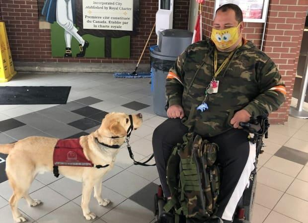 Cody Richards with his service dog Alder at the foot of the City Market in Saint John.  (Mia Urquhart/CBC - image credit)