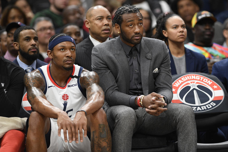 Washington Wizards guard Bradley Beal, left, and guard John Wall, right, watch from the bench during the second half of an NBA basketball game against the Milwaukee Bucks, Monday, Feb. 24, 2020, in Washington. The Bucks won 137-134 in overtime. (AP Photo/Nick Wass)