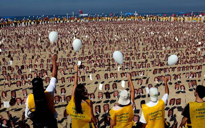 Members of the Baha'i religion demonstrate in Rio de Janeiro's Copacabana beach on June 19, 2011 asking Iranian authorities to release seven Baha'i prisoners accused of spying for Israel and sentenced to 20 years in jail - AFP
