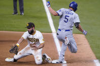 San Diego Padres' Eric Hosmer, left, tries to control the ball as Los Angeles Dodgers' Corey Seager (5) safely reaches first on a throwing error by Fernando Tatis Jr. during the third inning in Game 3 of a baseball National League Division Series Thursday, Oct. 8, 2020, in Arlington, Texas. (AP Photo/Tony Gutierrez)