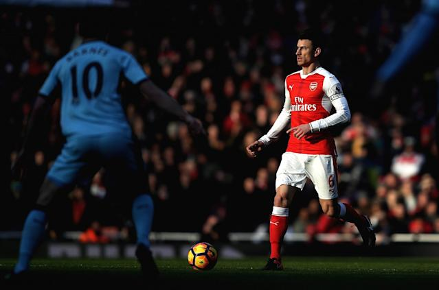 <p>Laurent Koscielny takes the ball out of defence for the Gunners </p>