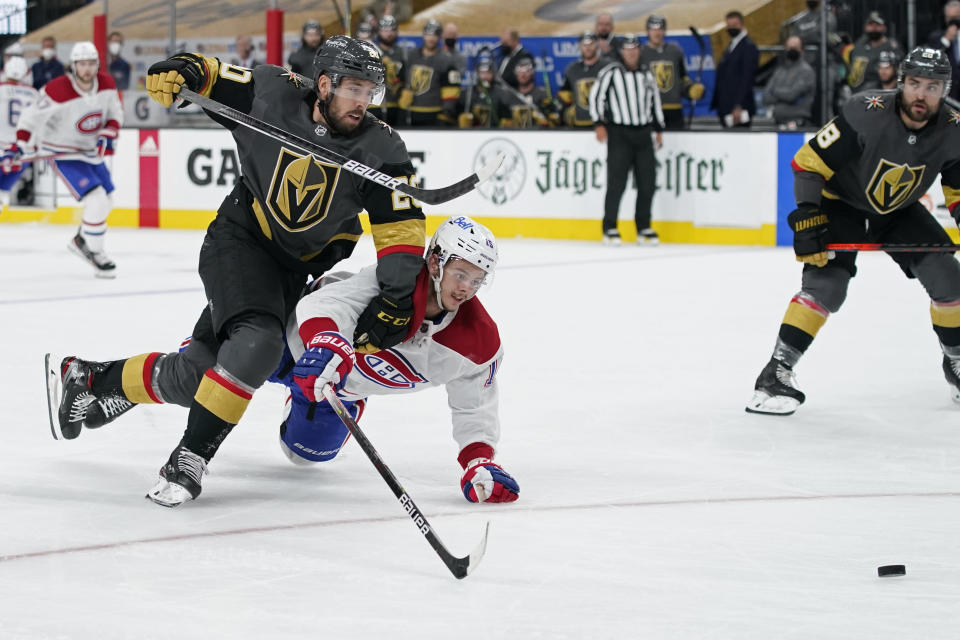 Vegas Golden Knights center Chandler Stephenson (20) and Montreal Canadiens center Jesperi Kotkaniemi (15) battle for the puck as they race down ice during the third period in Game 5 of an NHL hockey Stanley Cup semifinal playoff series Tuesday, June 22, 2021, in Las Vegas. (AP Photo/John Locher)