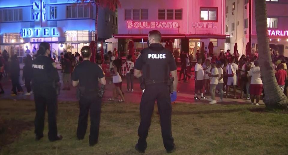 In this image taken from video, police stand guard on March 20, 2021, as crowds descend on South Beach in Miami.