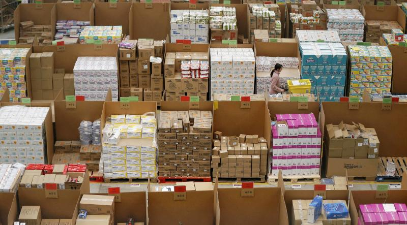 A member of staff pushes a trolley as she collects orders at the Amazon fulfilment centre in Peterborough