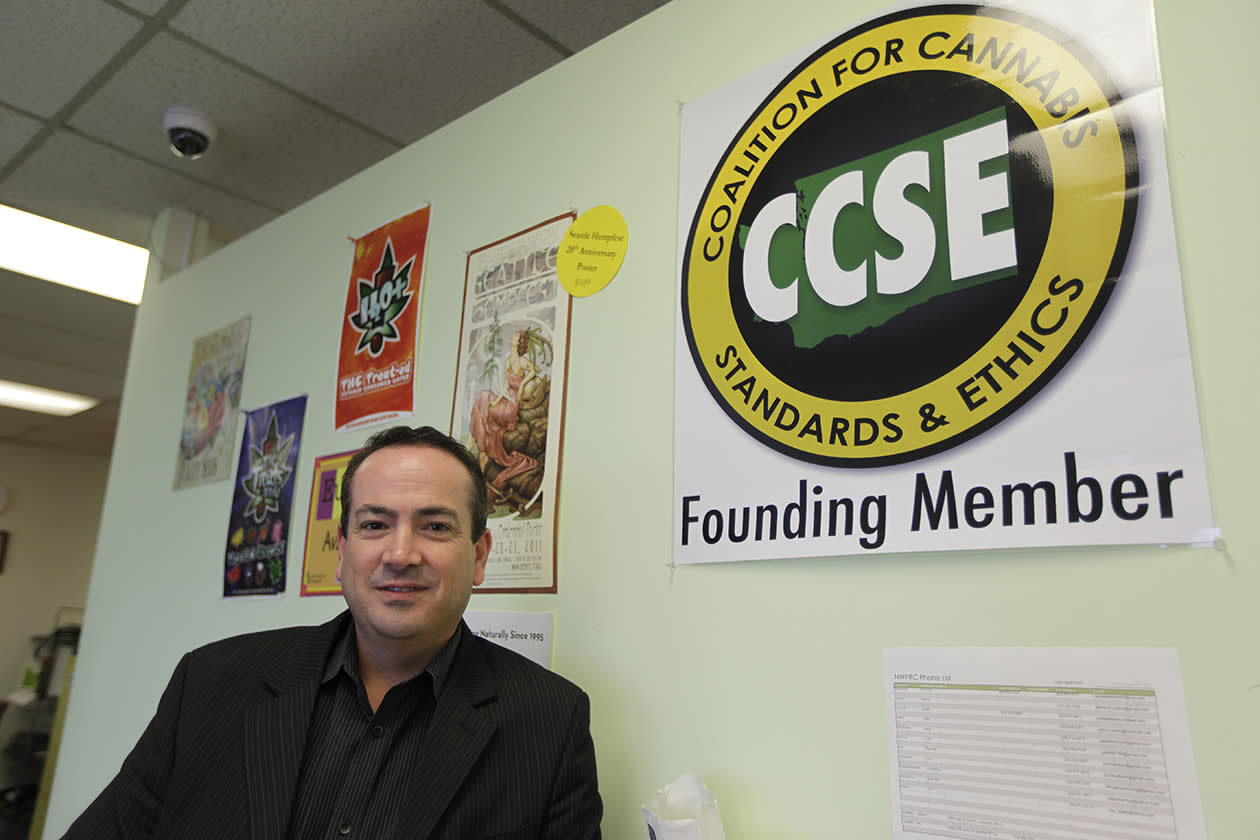 John Davis, chairman of the Coalition for Cannabis Standards and Ethics self-regulating trade organization, and co-owner of the Northwest Patient Resource Center medical marijuana dispensary, poses for a photo next to the CCSE certification logo, at his dispensary in Seattle. After voters weighed in on election day, Colorado and Washington became the first states to allow pot for recreational use, but they are likely to face resistance from federal drug warriors. Davis, who says it would make sense for his business to evolve from serving medical patients to the general public, says that the CCSE has offered to work with Washington state regulators to help them develop policy and legal guidelines relating to the legal use of marijuana.