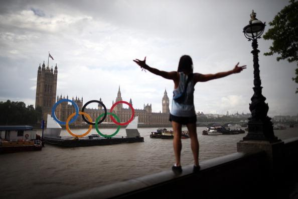 LONDON, ENGLAND - AUGUST 05:  A tourist gestures in a rain shower as he looks at giant Olympic rings in the River Thames opposite Parliament on August 5, 2012 in London, England.  (Photo by Peter Macdiarmid/Getty Images)