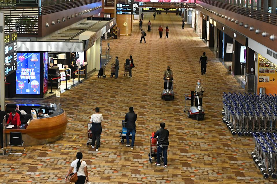 People walk along the transit hall at Changi International Airport in Singapore on January 7, 2021. (Photo by Roslan Rahman / AFP) (Photo by ROSLAN RAHMAN/AFP via Getty Images)