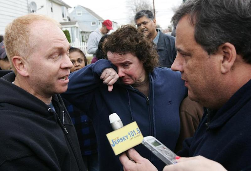 Annmarie Pansini, center, cries as New Jersey Gov. Chris Christie, right, speaks to her husband, Michael Pansini, during a tour of flood-ravaged Moonachie, N.J. Thursday, Nov. 1, 2012. The flooding of Moonachie, Little Ferry and Carlstadt, three communities sandwiched between Teterboro Airport, MetLife Stadium and the Hackensack River, was caused by six dirt berms that broke from the pressure of a tidal surge, Christie said. More than 1.7 million customers in New Jersey remain without power _ down from over 2.7 million at the height of the outages. (AP Photo/The Record of Bergen County, Kevin R. Wexler, Pool)