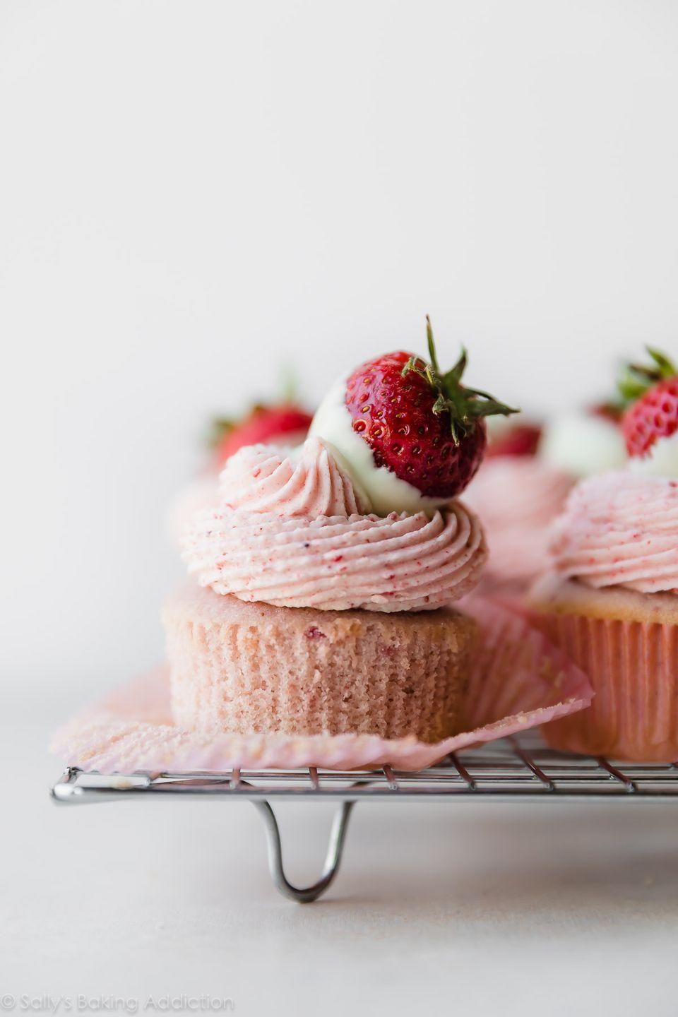 """<p>This recipe uses fresh strawberries in the cake and frosting. The chocolate-covered strawberry on top is so cute!</p><p><strong>Get the recipe at <a href=""""https://sallysbakingaddiction.com/white-chocolate-strawberry-cupcakes/"""" rel=""""nofollow noopener"""" target=""""_blank"""" data-ylk=""""slk:Sally's Baking Addiction"""" class=""""link rapid-noclick-resp"""">Sally's Baking Addiction</a>.</strong></p><p><strong><a class=""""link rapid-noclick-resp"""" href=""""https://go.redirectingat.com?id=74968X1596630&url=https%3A%2F%2Fwww.walmart.com%2Fbrowse%2Fhome%2Fbaking-pastry-tools%2Fthe-pioneer-woman%2F4044_623679_8455465_9246304%2FYnJhbmQ6VGhlIFBpb25lZXIgV29tYW4ie&sref=https%3A%2F%2Fwww.thepioneerwoman.com%2Ffood-cooking%2Fmeals-menus%2Fg35139389%2Fvalentines-day-cupcake-ideas%2F"""" rel=""""nofollow noopener"""" target=""""_blank"""" data-ylk=""""slk:SHOP BAKING TOOLS"""">SHOP BAKING TOOLS</a><br></strong></p>"""