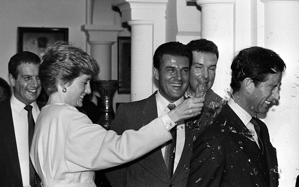 <p>The Princess of Wales smashes an imitation bottle made of sugar glass over the head of the Prince of Wales during the couples visit to the set of The Living Daylights.</p>