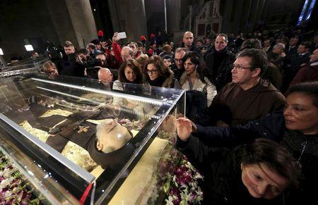 Faithful surround the exhumed body of the mystic saint Padre Pio in the Catholic church of San Lorenzo fuori le Mura in Rome, February 3, 2016.  REUTERS/Yara Nardi