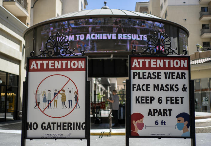 FILE - In this June 11, 2021, file photo, signs with social distancing guidelines and face mask requirements are posted at an outdoor mall amid the COVID-19 pandemic in Los Angeles. Los Angeles County residents are again required to wear masks indoors regardless of their vaccination status, a new mandate starting this weekend that health officials hope will reverse the latest spikes in coronavirus cases, hospitalizations and deaths. The rule went into effect late Saturday, July 17, for the nation's largest county, home to 11 million people, where a sharp increase in COVID-19 cases is led by the highly transmissible delta variant. (AP Photo/Damian Dovarganes, File)