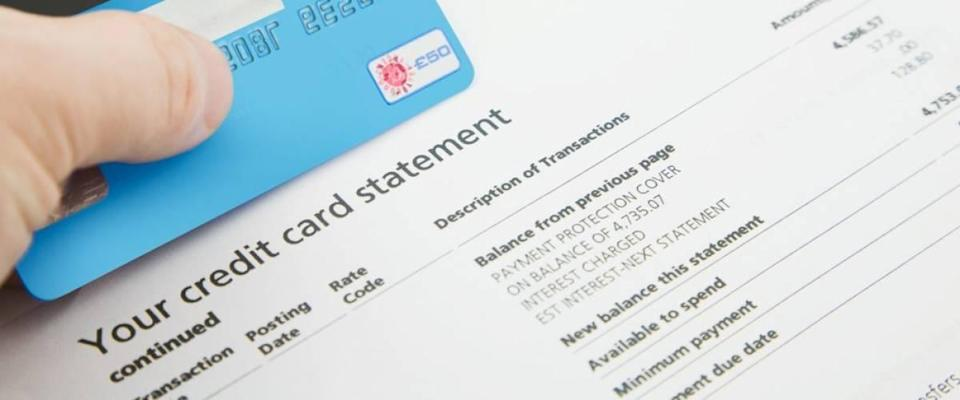 A credit card statement with a hand holding a blue credit card