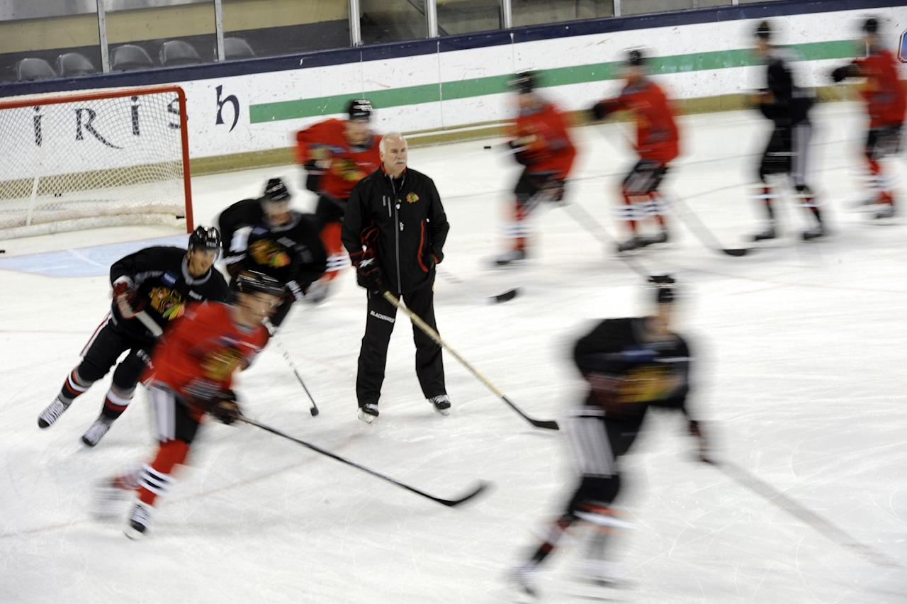 Chicago Blackhawks players skate past coach Joel Quenneville at the teams NHL hockey training camp on the campus of the University of Notre Dame in South Bend, Ind., Thursday, Sept. 12, 2013. (AP Photo/Joe Raymond)